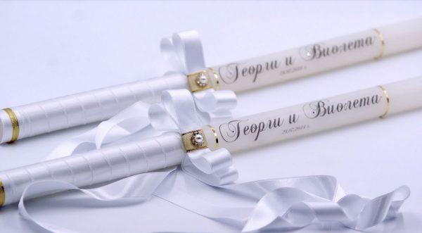 Сватбени бели свещи със златни елементи, елегантно декорирани със сатенена лента и красиви надписи.