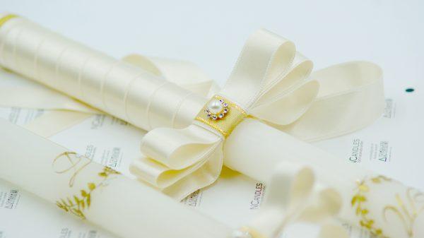 Сватбени свещи с инициали в лавров венец - красияо изрисувани в цвят злато. Украсата на свещите се допълва от сатенена лента и панделка с перла .
