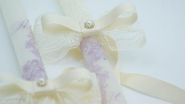 Бели сватбени свещи с инкрустирана лилава дантела и инициали на младоженците. Допълнително украсени с дантела в цвят айвъри и добавени камъчета Swarovski.