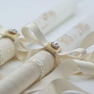 Сватбени свещи в злато и нежна дантела. Това са елегантни свещи с изящен надпис в цвят злато и умело украсен с камъчета Swarovski. Дантелата завършва с панделка фиксирана с перла.